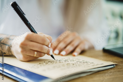Fotografie, Tablou  Front view of hands of lesbian bridal writing of vows in the notebook on the wod