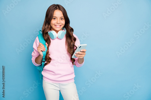 Obraz Photo of pretty small school lady hold telephone turning on popular youth song wireless earflaps wear rucksack casual hoodie hood pink pullover isolated blue color background - fototapety do salonu