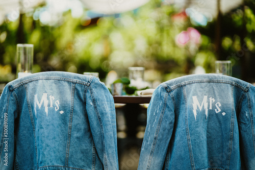 Photo Bridal jeans jackets are hanging on the chairs backs outdoors on the sunny day
