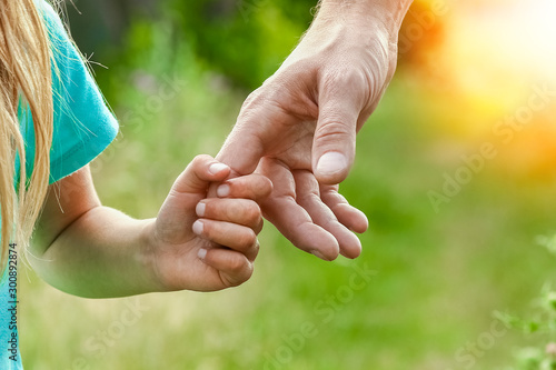 Valokuva  hands of parent and child in nature