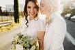 canvas print picture - Just married lesbian couple is hugging outdoors and holding big bridal bouquet