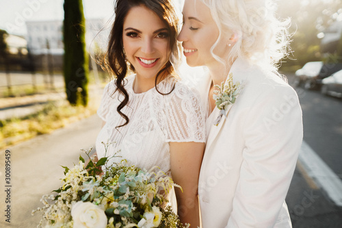 Fotomural  Just married lesbian couple is hugging outdoors and holding big bridal bouquet