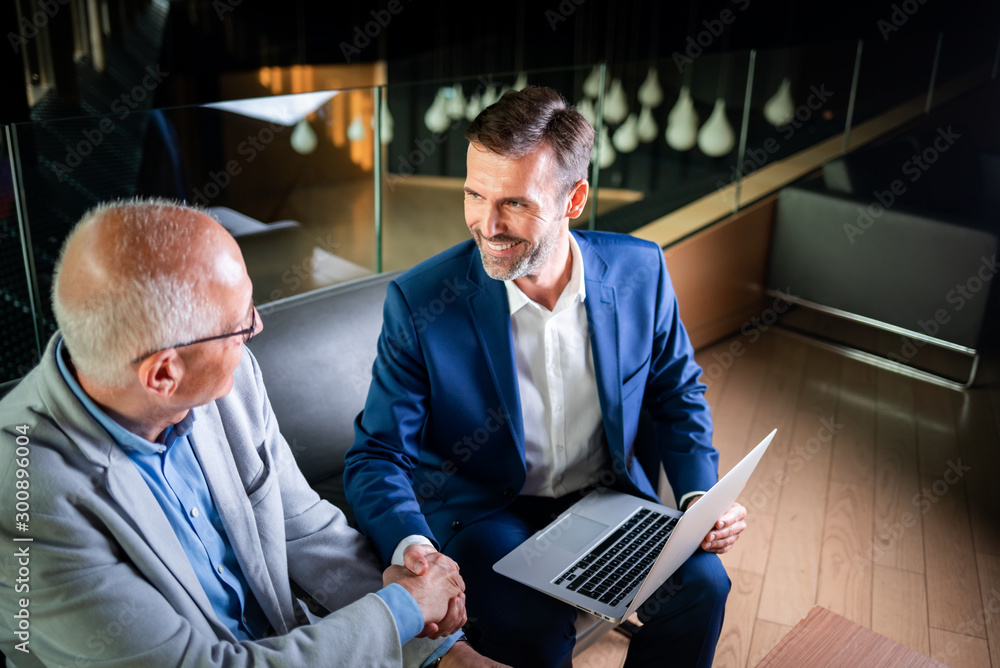 Fototapeta Younger and older businessman shaking hands in modern business lounge