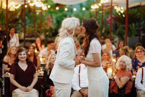 Fotografía  First kiss of a lesbian couple in front of crowd of guests at the decorated terr