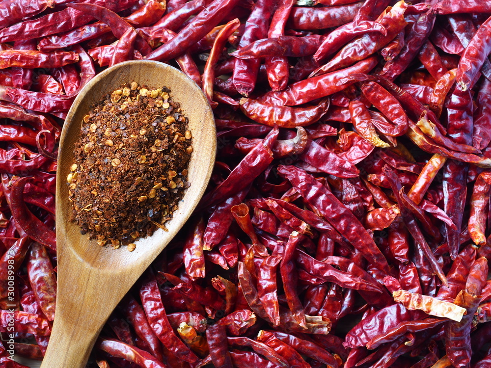 Fototapeta Red Chili powder in wooden spoon on Dry hot chillis background, Food ingredient.