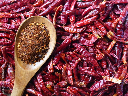 Photo  Red Chili powder in wooden spoon on Dry hot chillis background, Food ingredient
