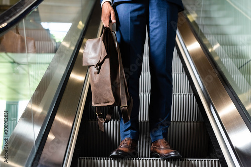 Photographie cropped view of man holding backpack on escalator in hotel