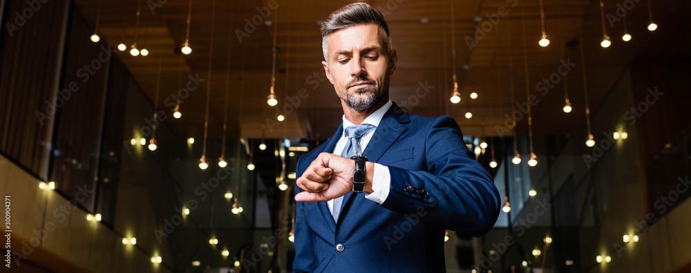 Fototapeta panoramic shot of businessman in suit looking at watch