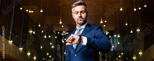 Fotografía panoramic shot of businessman in suit looking at watch