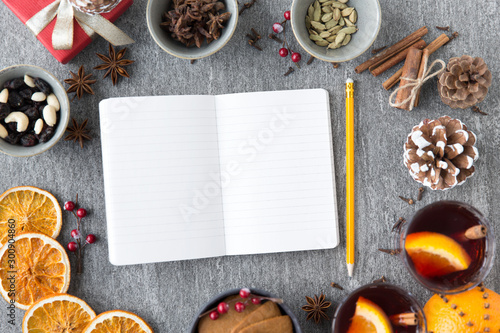 christmas, winter holidays and new start concept - notebook with pencil, hot mulled wine and aromatic spices on grey background