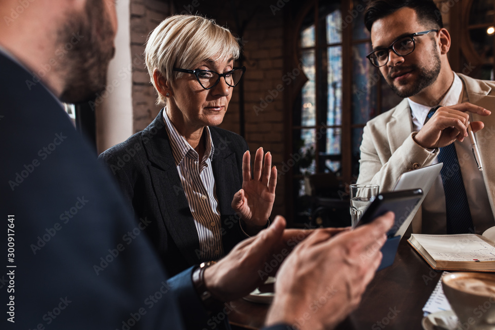 Fototapeta Senior businesswoman holding a meeting with her younger colleagues at office cafeteria.