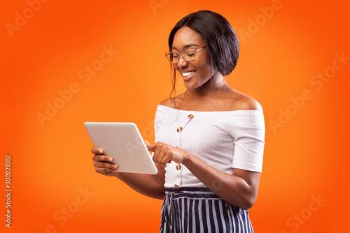 Tablou Canvas Happy African American Woman Using Digital Tablet Standing, Studio Shot