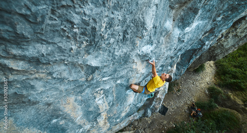 Fototapeta top view of man rock climber in yellow t-shirt, climbing on a cliff, searching, reaching and gripping hold. Conquering, overcoming and active lifestyle concept. obraz