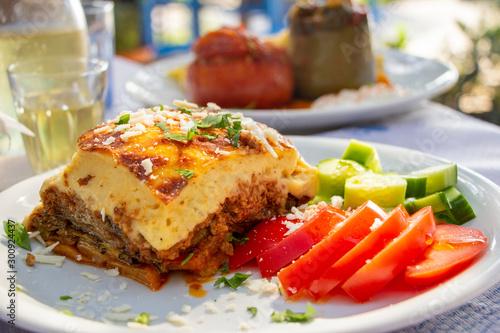 Fototapeta Greek traditional moussaka on a white plate served in taverna, Greece obraz