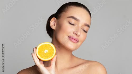 Cuadros en Lienzo Beautiful pretty woman holding half of orange