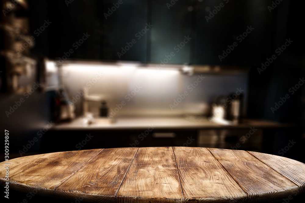 Fototapeta Wooden table background of free space for your decoration and blurred background of kitchen. Copy space.Dark mood interior. Kitchen furniture.