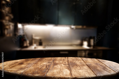 Obraz Wooden table background of free space for your decoration and blurred background of kitchen. Copy space.Dark mood interior. Kitchen furniture.  - fototapety do salonu