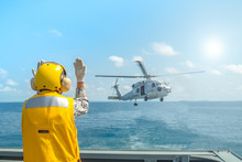 Signal Man Give Signal Hand To A Military Navy Helicopter Above Aviation Deck On The Ocean.