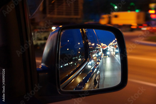 reflection in the side mirror of car traffic in the evening