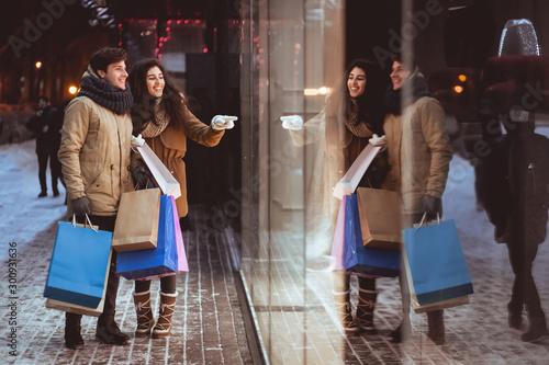 Fotografía  Girl Pointing At Shopwindow Shopping With Boyfriend In Night City