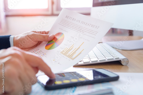 Fotografia Businessman or analyst reviewing financial report on investment risk and a return on investment analysis with smartphone application touch screen
