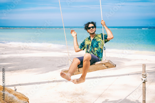 Stylish happy sexy young brunette man with a beard in a Hawaiian shirt is swinging on a swing on the tropical sea