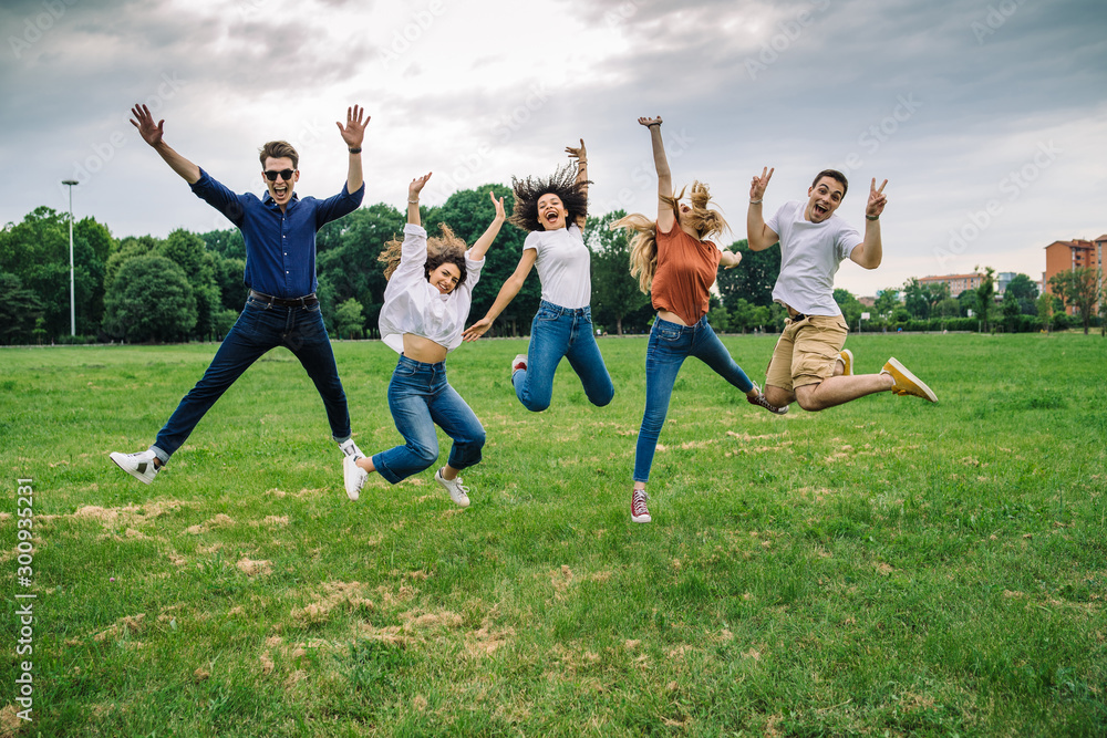 Fototapeta Group of five friends jump into the air with their hands up - Millennials have fun together at the park in the summer