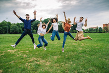 Group Of Five Friends Jump Into The Air With Their Hands Up - Millennials Have Fun Together At The Park In The Summer