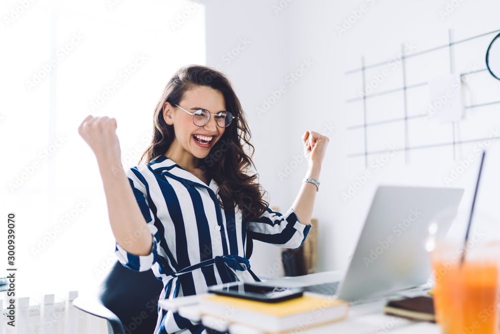 Fototapeta Happy young woman sitting at table with hands up in winner gesture