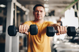 authentic image, fit coach man lifting weight, training bicep curl in the gym. concept of weight loss and healthy living. selective focus - focus is on the dumbbells.