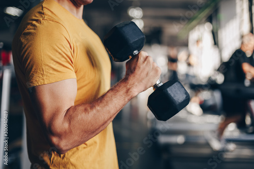 authentic image, detail close up of fit coach man lifting weight, training bicep curl in the gym Fototapeta