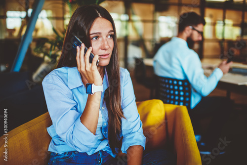 Frustrated hipster girl casual dressed have serious telephone conversation received unhappy news from work, sad confused woman making trouble smartphone call using wireless connection indoors