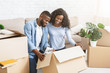 Excited african american couple unpacking stuff after moving in