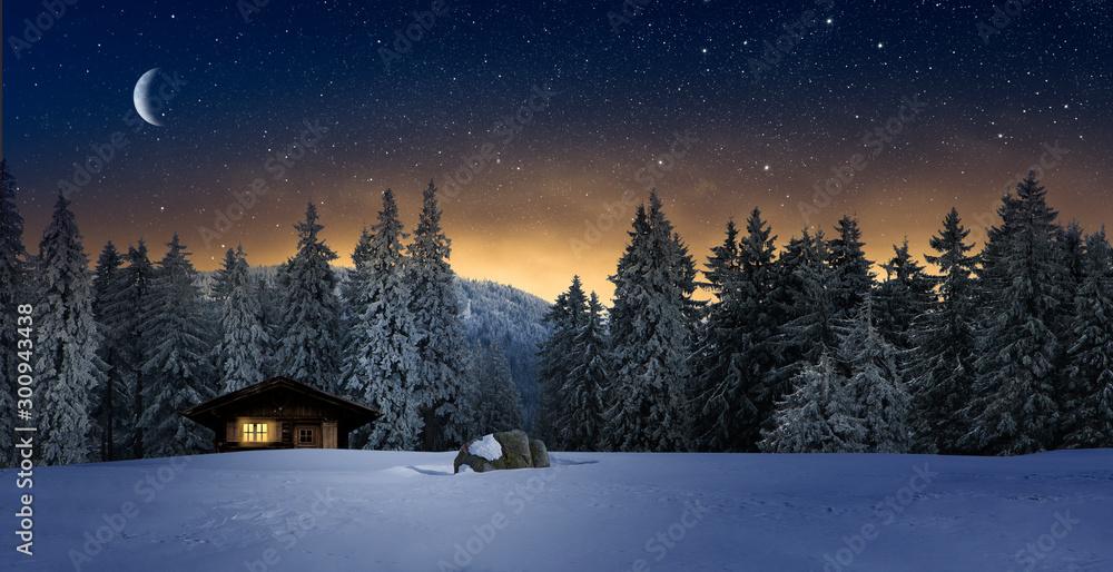 Fototapeta Gemütliche Holzhütte mit Beleuchtetem Fenster in Wnterwald bei Nacht im Winter
