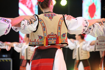 Dancers hold hands in a traditional Romanian dance wearing traditional beautiful costumes.