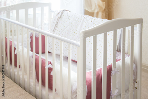 Fotografering Baby bed crib with white and Burgundy color pillows with laces