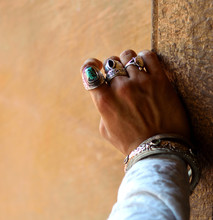 Close Up Of Man's Hand Wearing Rings And Bracelets
