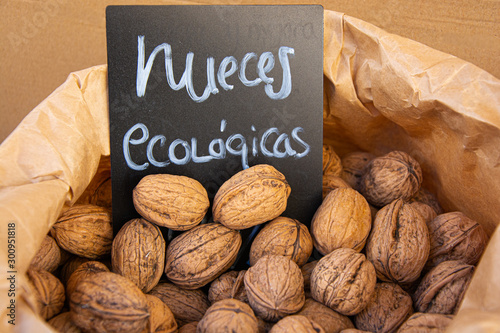 Obraz na plátně  Walnuts in open paper sack to expose walnuts with organic walnut sign, overhead view, brown tones