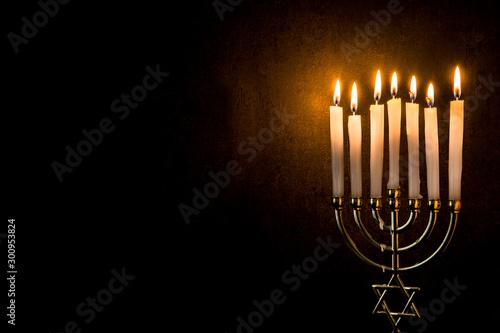 Valokuva  Jewish Hanukkah menorah on black background. Copy space