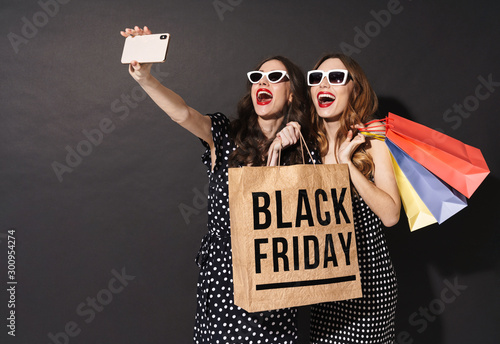Obraz Image of girls taking selfie on cellphones and holding black friday bag - fototapety do salonu