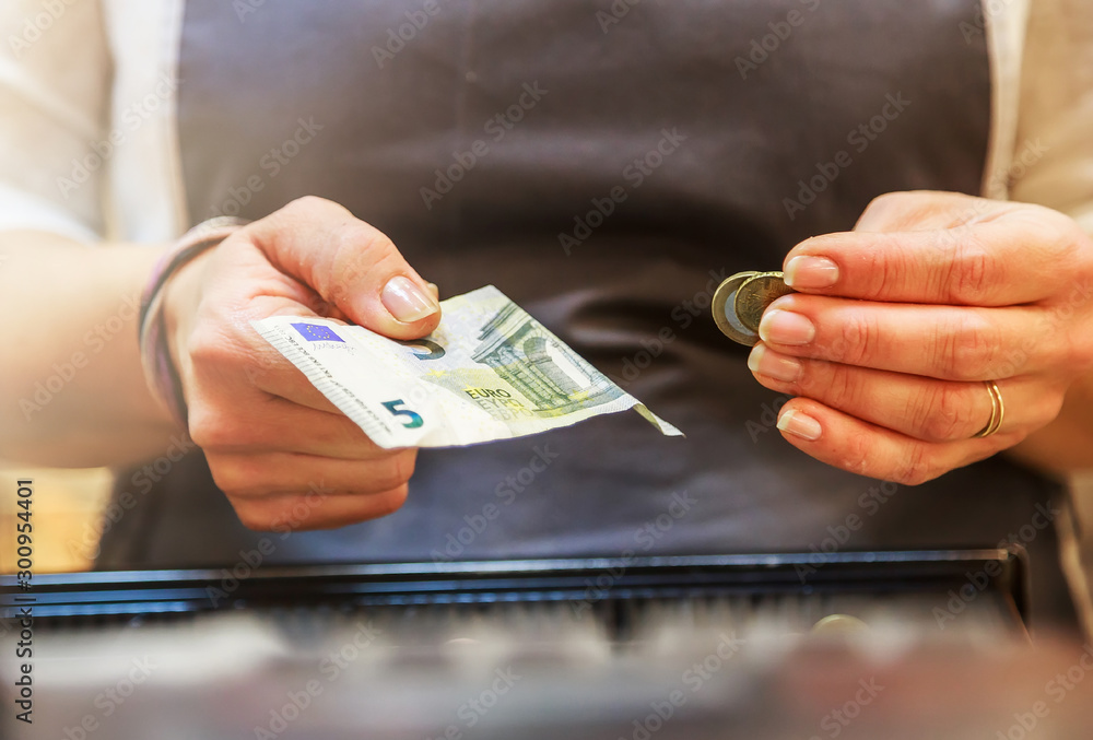 Fototapeta woman is paying In cash with euro banknotes