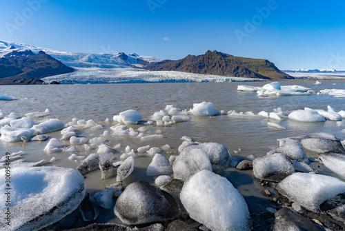 Icebergs on Jokulsarlon glacier lagoon with Vatnajokull glacier in the background