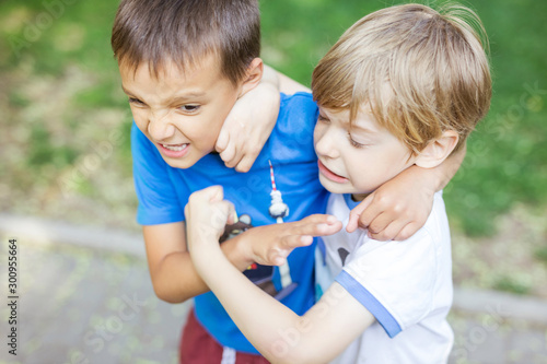 Fototapeta Two boys fighting outdoors. Siblings rivalry.