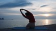 Slim lady silhouette in sportswear sitting in sea water stretches perfect body against breathtaking sunset backside view