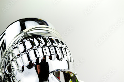 Fotomural Upside down teeth of a shiny chrome effect skull mask taken in a studio with studio lighting