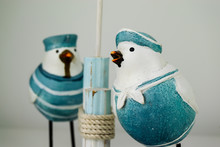 Two White Bird Ornaments Dressed In Sailor Type Uniforms Next To Wooden Upright Poles Taken Against A White Background.