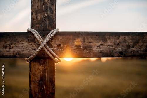 Fototapeta Closeup shot of a wooden cross with the sun in the blurred background