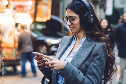 Fotografija Happy young female enjoying listening to music through headphones outside