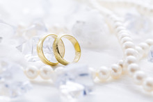Two Golden Rings With Pearl Necklace And On White Background