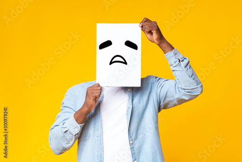 African american guy hiding face behind paper with sad emoticon Wallpaper Mural